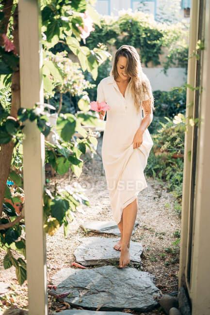 Fröhliche Frau steht im Glashaus-Eingang — Stockfoto