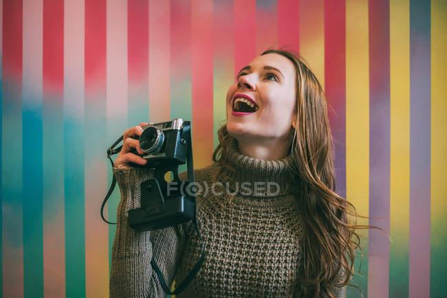 Jovem feliz segurando câmera vintage contra fundo colorido listrado — Fotografia de Stock