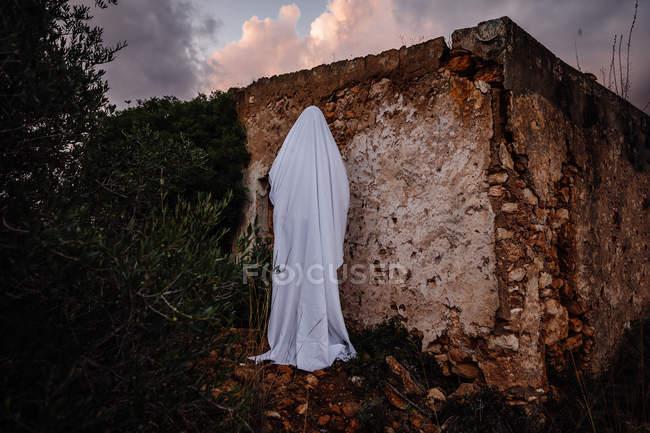 Personne déguisé en fantôme pour moyenne Halloween à côté de la maison en ruine — Photo de stock
