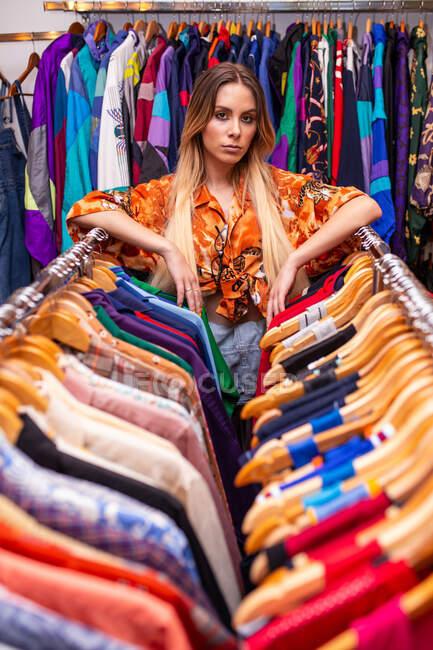 Красивая молодая женщина опирается на перила одежды и смотрит в камеру, стоя в маленьком магазине — стоковое фото