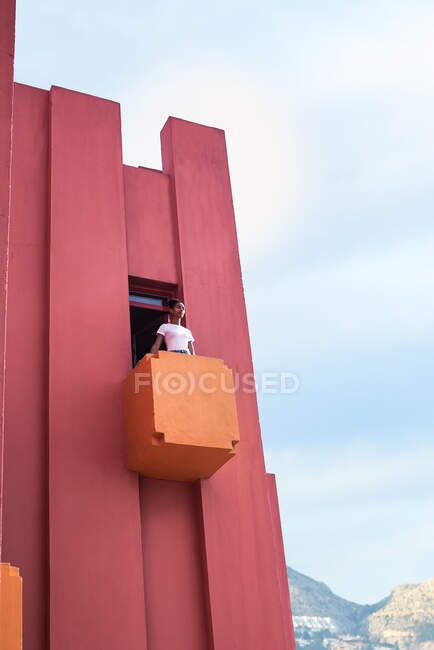 Black woman standing in a colorful geometric building windows — Stock Photo