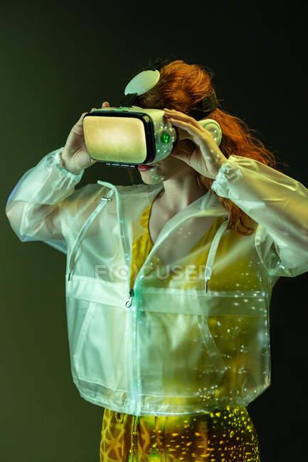 Женщина в очках VR, стоящая в теплых светлых пятнах — стоковое фото