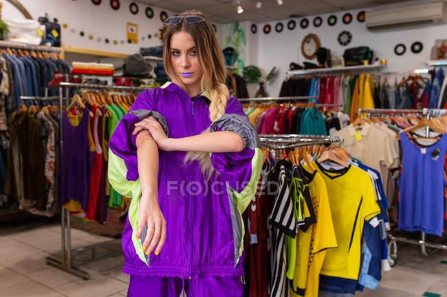 Красивая молодая женщина в ярком модном наряде, держась за руки в карманах и глядя в камеру, стоя рядом с перилами одежды в маленьком магазине — стоковое фото