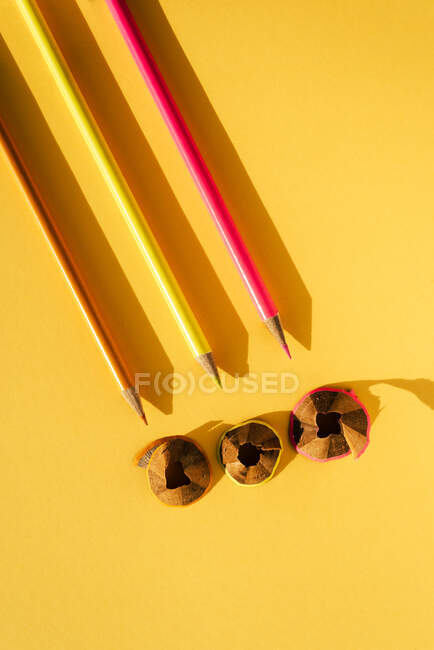 Three colored pencils and shavings, on yellow background — Stock Photo