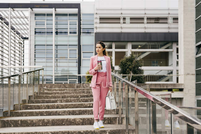 Young elegant woman wearing pink suit with white sneakers walking downstairs with coffee cup in front of office building — Stock Photo