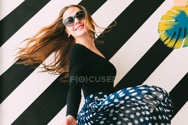 Cheerful young woman dancing against colorful wall — Stock Photo