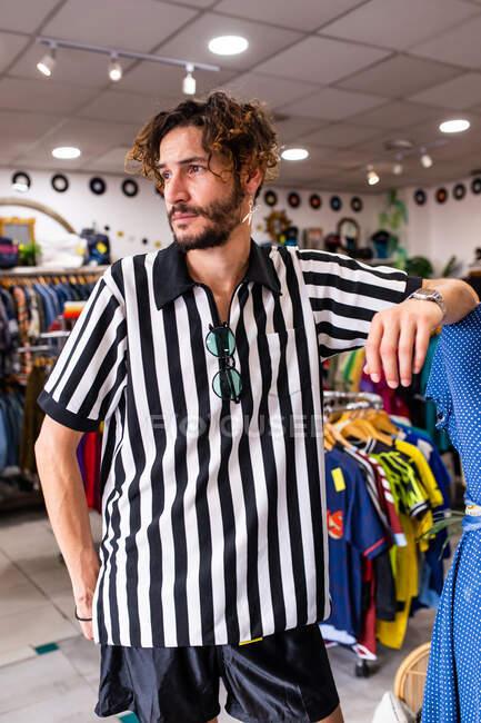 Веселый человек в магазине смотрит в сторону — стоковое фото