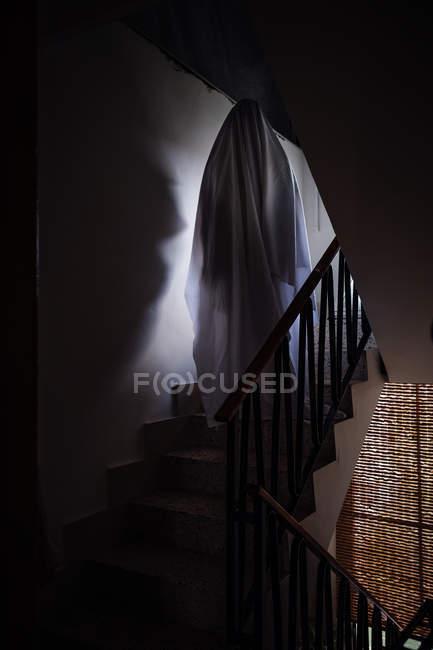 Personne déguisé en fantôme pour Halloween en chambre noire — Photo de stock