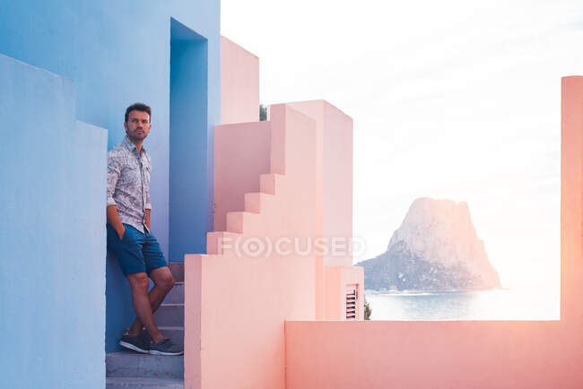 Thoughtful man leaning in a blue and pink building wall — Stock Photo