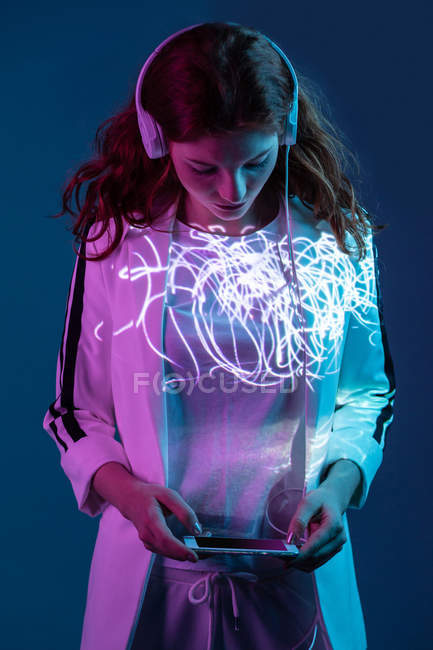 Woman listening to music and using smartphone in neon light stains — Stock Photo