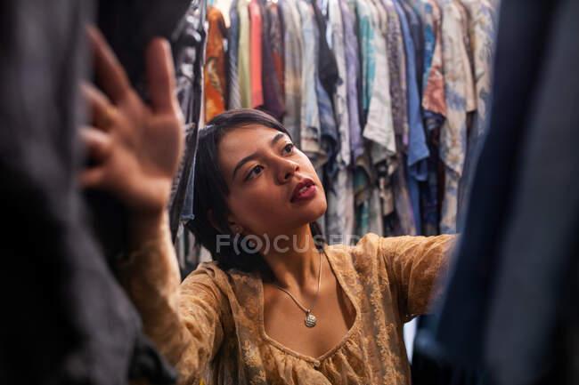Привлекательная юная леди ищет новый наряд на перилах одежды в маленьком магазине — стоковое фото
