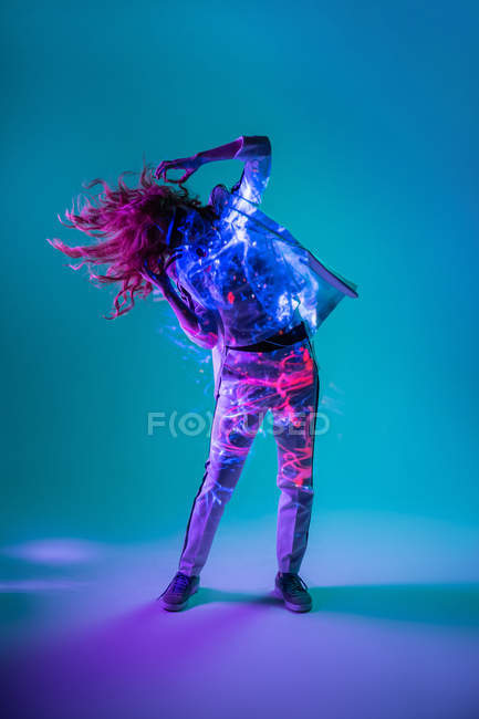 Woman dancing in neon light on blue background — Stock Photo