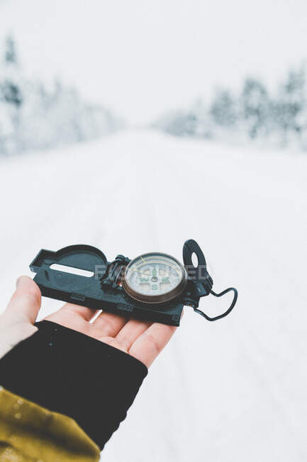 Crop hand of traveler holding compass on background of snowy nature in daylight - foto de stock