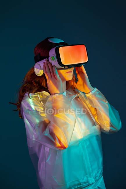 Frau mit Vr-Brille im Licht auf blauem Hintergrund — Stockfoto