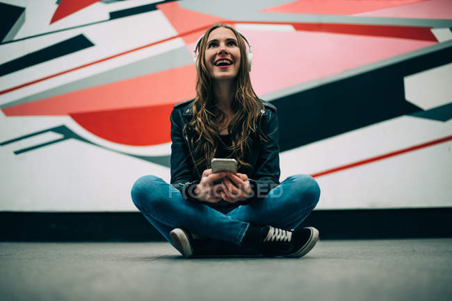 Happy young woman sitting on floor with mobile phone and listening to music against colorful background — Stock Photo