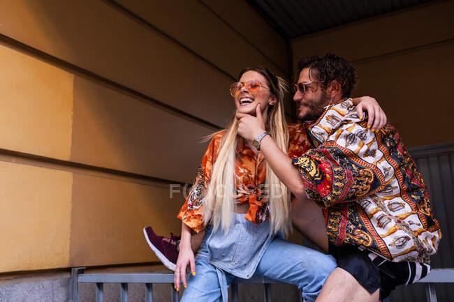 Jovem e mulher em roupas da moda sentado em cerca de metal na rua da cidade e olhando para a câmera — Fotografia de Stock