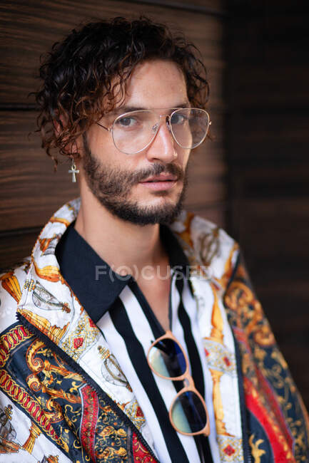 Handsome young guy with curly hair wearing trendy clothes and looking at camera while standing on blurred background of wall — Stock Photo