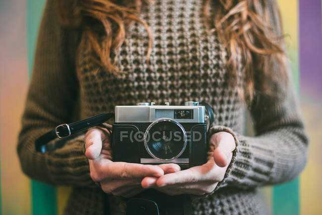 Close-up of woman in brown sweater holding vintage camera — Stock Photo