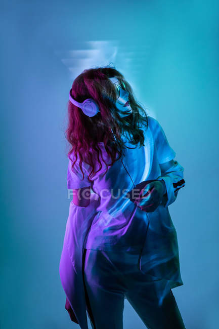 Woman enjoying music with headphones in neon light — Stock Photo