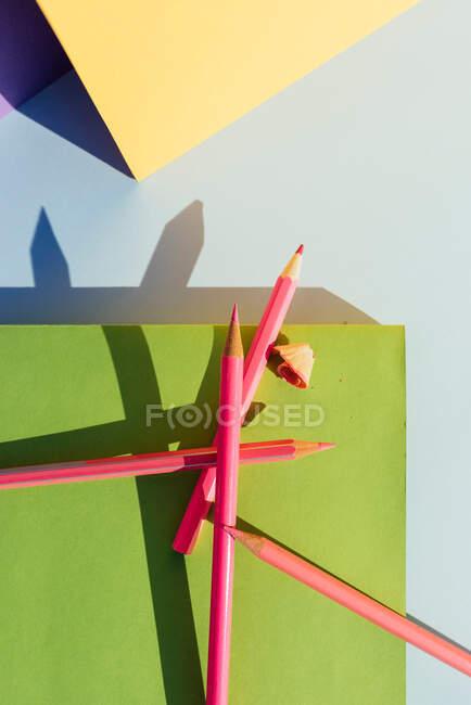 Lápices rosados sobre libro verde, en espacio de formas geométricas y fuertes sombras. Concepto de regreso a la escuela - foto de stock
