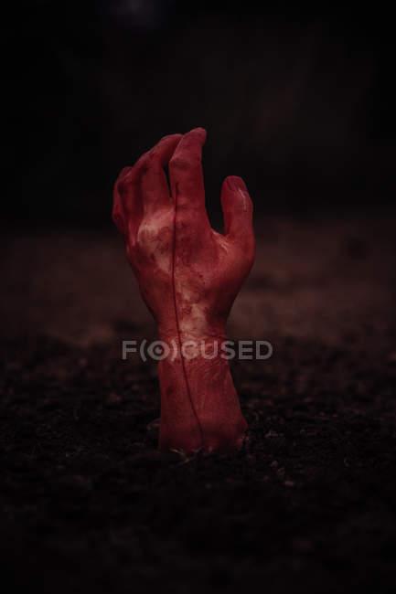 Main de zombie sortant du sol sur fond sombre — Photo de stock