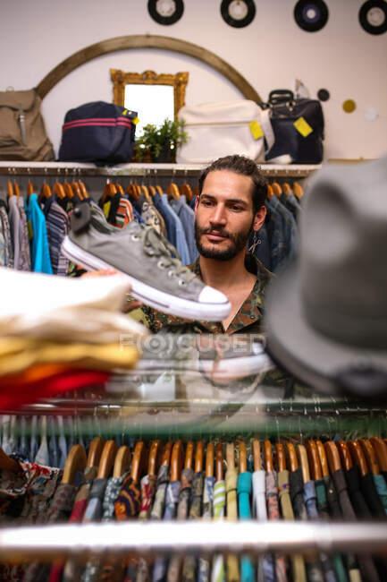 Beau jeune homme regardant des chaussures tout en choisissant de nouvelles baskets dans un petit magasin de vêtements — Photo de stock