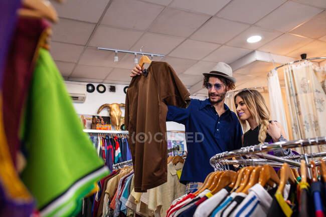 Поручний чоловік вибирає стилістичну сорочку, проводячи час у маленькому магазині з подругою. — стокове фото