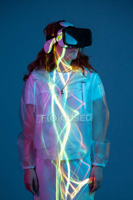 Woman in VR glasses standing in neon light stripes — Stock Photo