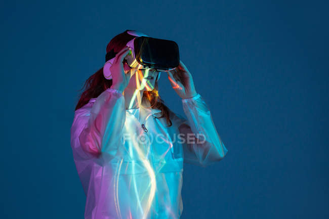 Woman using VR glasses in neon light stripes — Stock Photo