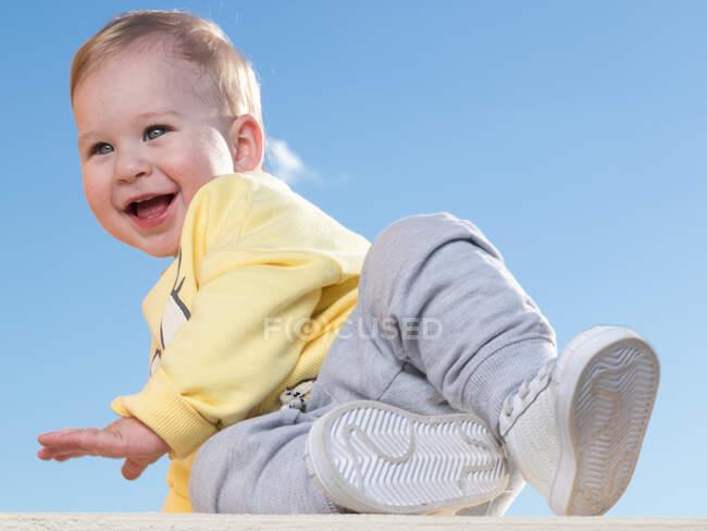 Alegre pouco criança menino sentado em roupas casuais e se divertindo no fundo azul. — Fotografia de Stock