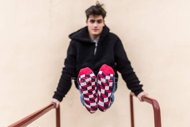 Молодой подросток тренируется и показывает разноцветные носки на бежевой стене — стоковое фото