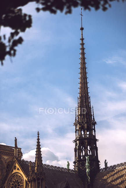 Pointed tower of Notre Dame de Paris at daylight on background of blue sky, Paris, France — Stock Photo