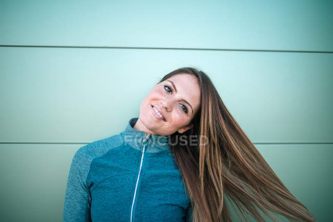 Portrait of young smiling woman in sports clothes standing in front of green wall — Stock Photo