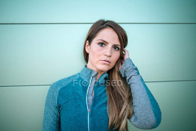 Portrait of young woman in sports clothes standing in front of green wall — Stock Photo