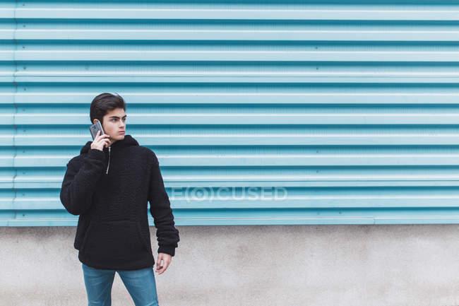 Giovane adolescente in piedi al muro di metallo e parlando sul telefono cellulare — Foto stock