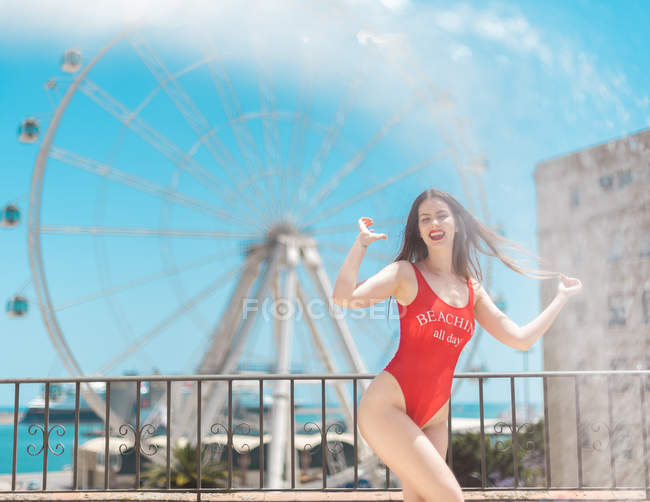Stylish young woman in red swimsuit standing on terrace with cityscape on background — Stock Photo