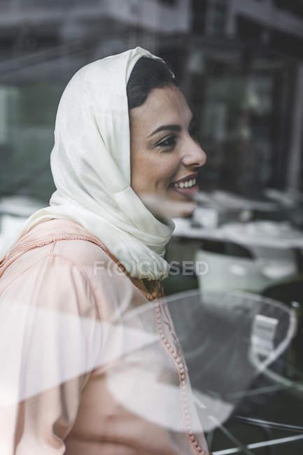 Lächelnd Marokkanerin mit Hijab sitzt hinter Fensterscheibe — Stockfoto