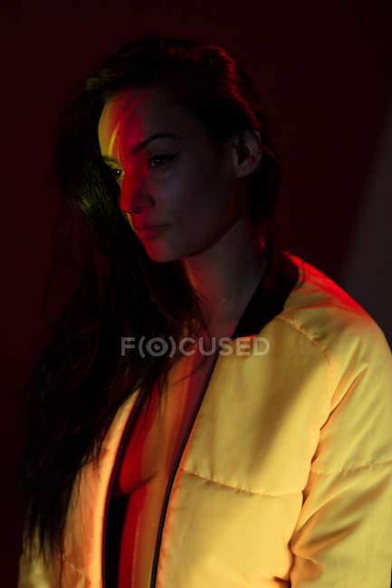 Mujer joven bonita en chaqueta blanca con manchas de luz en la cara - foto de stock