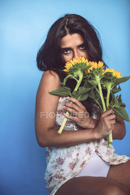 Young woman posing in studio with sunflowers on blue background — Stock Photo