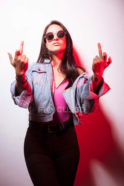 Contemptuous young pink dressed woman in sunglasses standing at white wall and showing middle fingers — Stock Photo