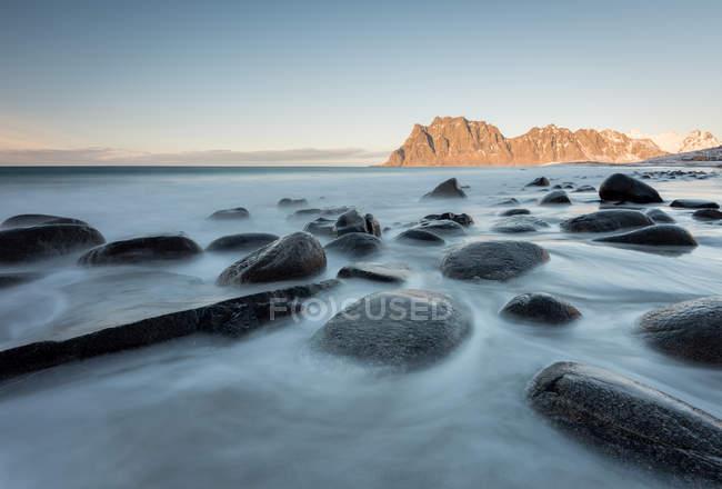 Smooth dark stones in long exposure flow of water on background of cliffs, Lofoten, Norway — Stock Photo