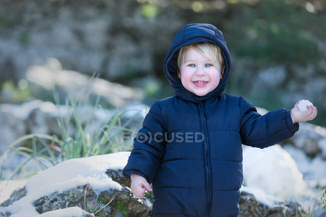 Cheerful little toddler boy looking at camera and holding snowball in nature. — Stock Photo
