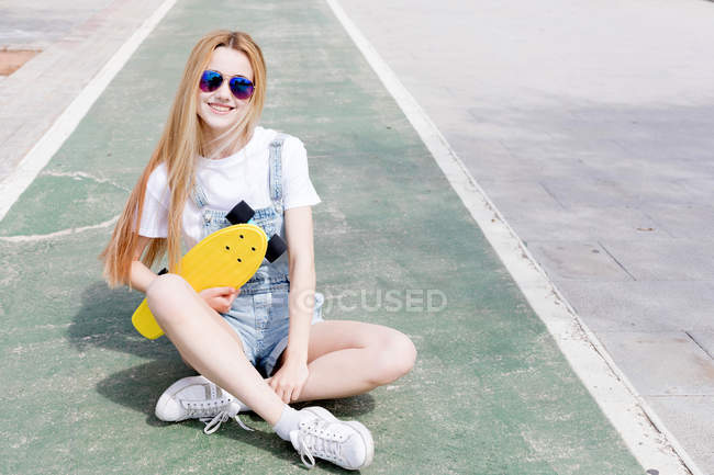 Blonde stylish girl sitting on skate park with penny board and looking at camera — Stock Photo