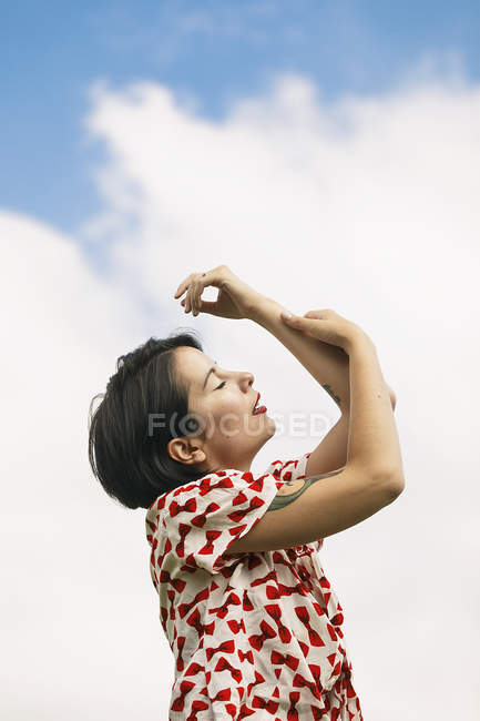 Emotional young woman in patterned dress posing against cloudy sky — Stock Photo