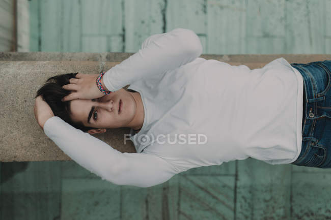 Young handsome man lying on concrete wall and covering eyes with hand — Stock Photo