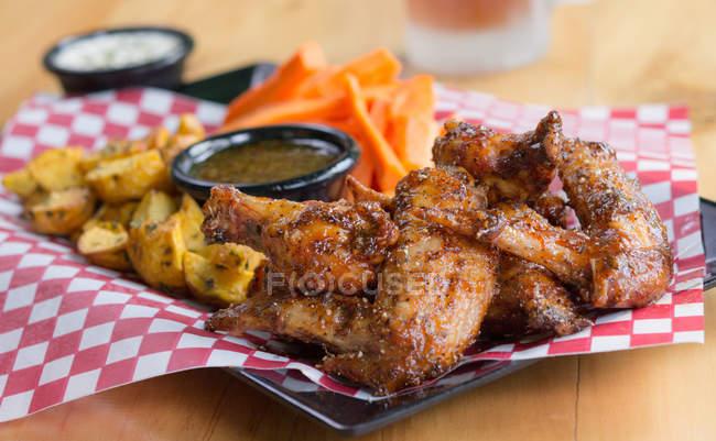 Вкусные свежие жареные куриные крылышки, подается с овощами и соусами на столе — стоковое фото