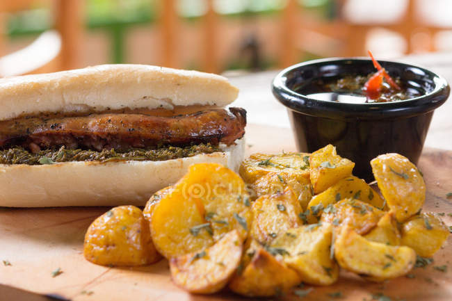 Appetizing fresh cooked burger served with sauce and potatoes — Stock Photo