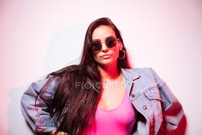 Young pink dressed woman in sunglasses standing at white wall and looking at camera — Stock Photo