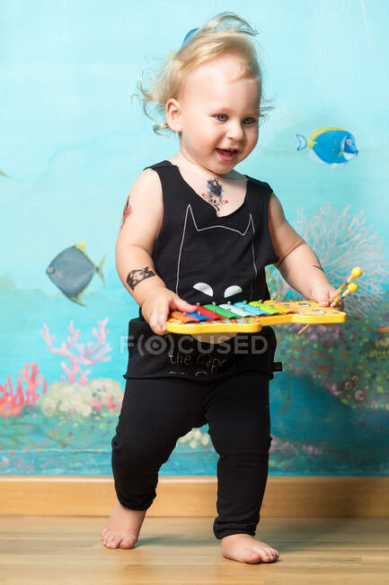 Класний маленький хлопчик з татуюваннями, що стоять з ксилофоном.. — стокове фото