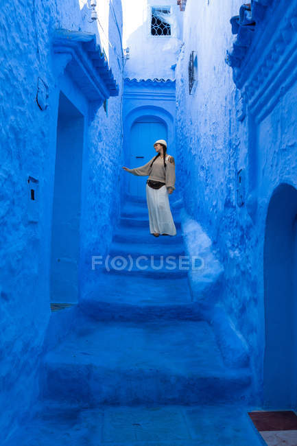 Woman wearing cap and long skirt walking on Moroccan city dyed blue — Stock Photo
